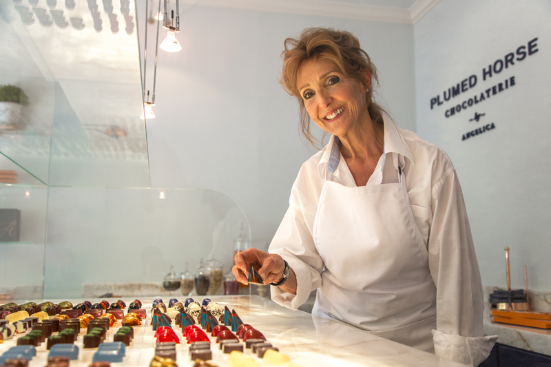 Angelica, proprietor of Plumed Horse Chocolaterie, displaying a counter covered with delicious looking chocolates.